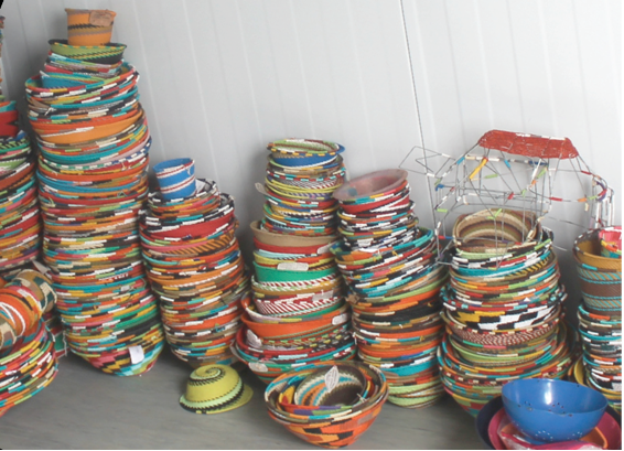 Photo caption: Virginia Semango displays bowls made by women from Muyexe Arts and Craft.