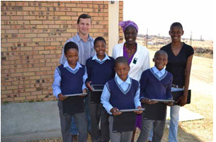 Mpumalanga iSchool coordinator Gerhard Oosthuizen, Vukuzenzele Combined School principal TE Mudau and National Rural Youth Services Corps participant Samukelisiwe Khumalo, with some the Grade 6 learners who are being taught with the help of iPads.