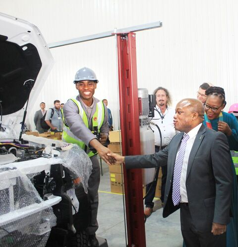 Sithembiso Mthembu employed at Mahindra Assembling Plant in Durban greeting the MEC for Economic Development, Tourism and Environmental Affairs Sihle Zikalala during the launch.