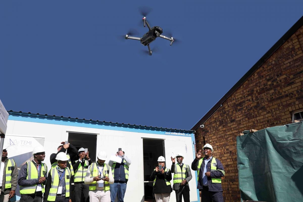 Officials of the DID test flying the drone which is planned to make the monitoring of infrastructure programmes more effective.