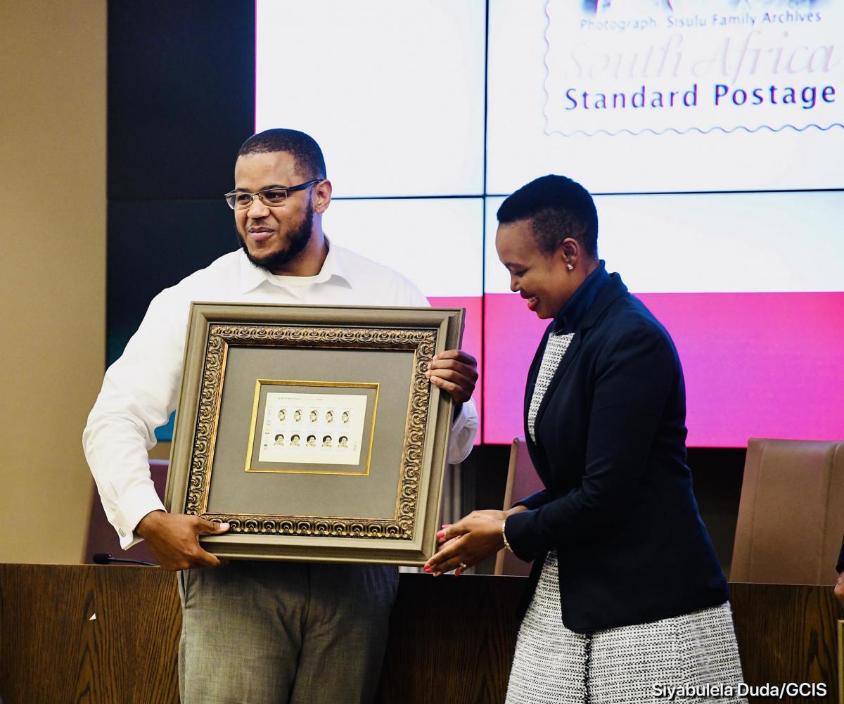 Communications Minister Stella Ndabeni-Abrahams hands over the centenary commemorative stamp of Albertina Sisulu to the struggle icon's grandson Duma Sisulu.