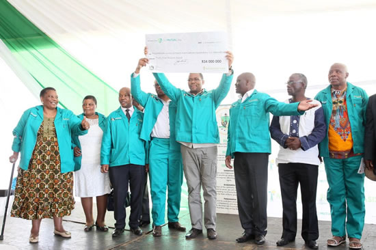 MEC Cyril Xaba holds a R34 million cheque to be shared between various cooperatives in the Harry Gwala Municipality.