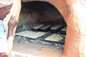 Lindiwe Nkosi checks bread and scones in the clay oven.