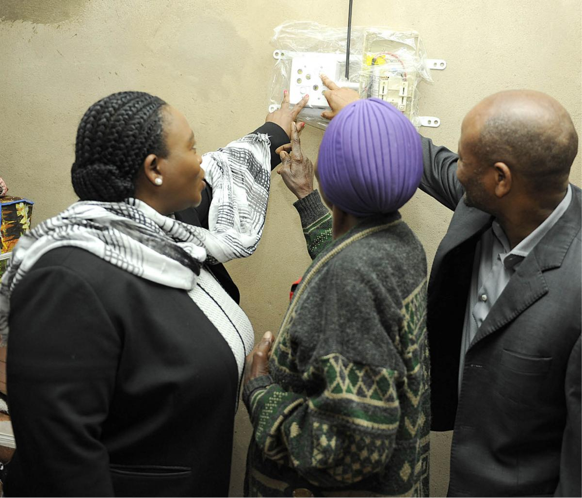 KZN Premier Senzo Mchunu and MEC for Cooperative Governance and Traditional Affairs Nomusa Dube-Ncube show Nozibulo Ntshangase how to load money on her electricity meter.