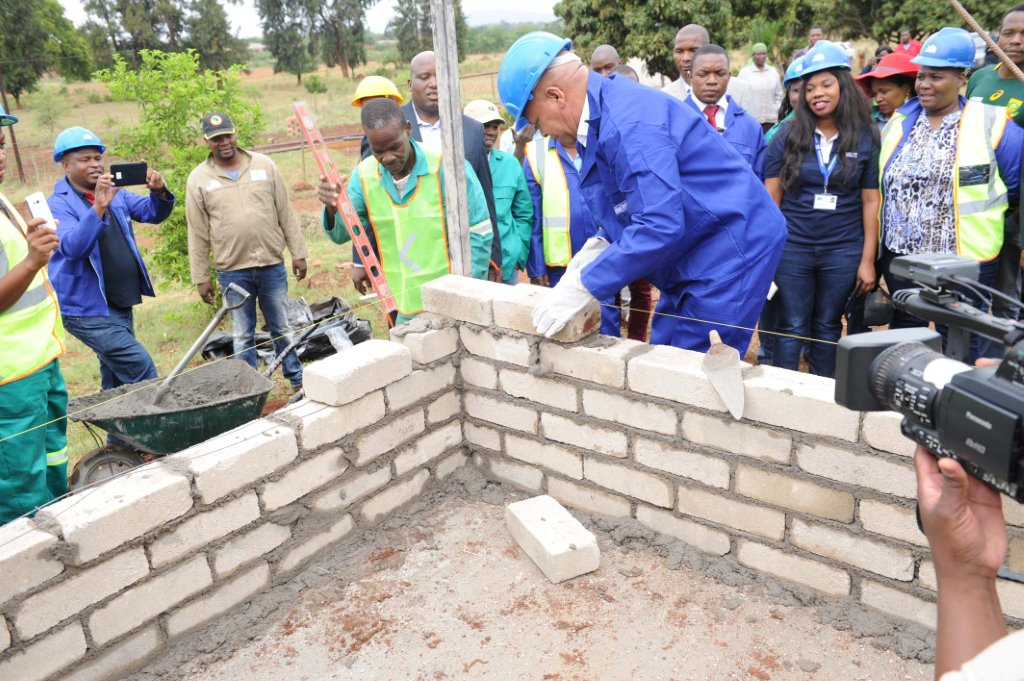Limpopo Premier Stanley Mathabatha lays a brick during the building phase of Lina Marutha's new home.
