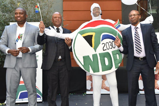 Deputy Minister Buti Manamela, Minister Jeff Radebe and Acting Director-General Tshediso Matona with the NDP mascot showing off the new logo.