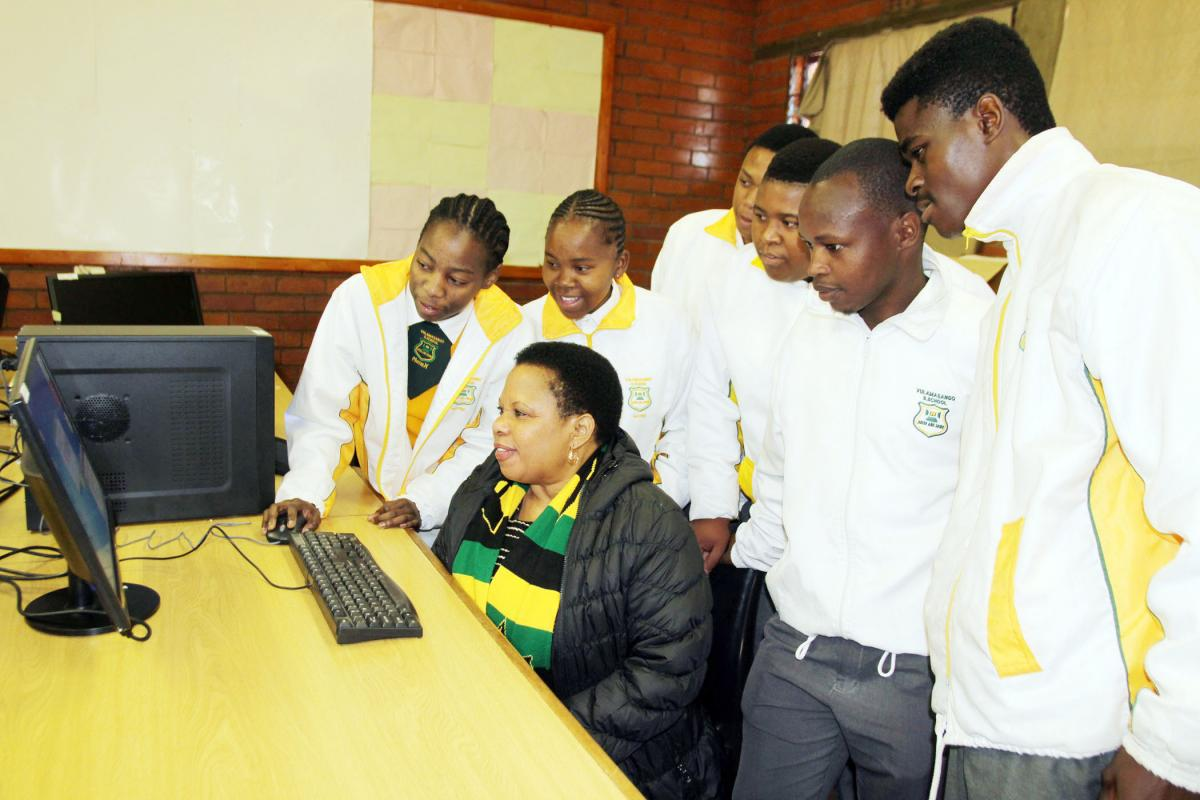 Deputy Minister Maggie Sotyu and learners at Vulamasango High School try out one of the new computers.