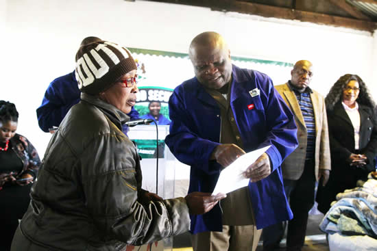MEC for Agriculture and Rural Development Themba Mthembu hands over one of 67 food vouchers to one of 67 families in Greytown. (Photo: KZNDARD)