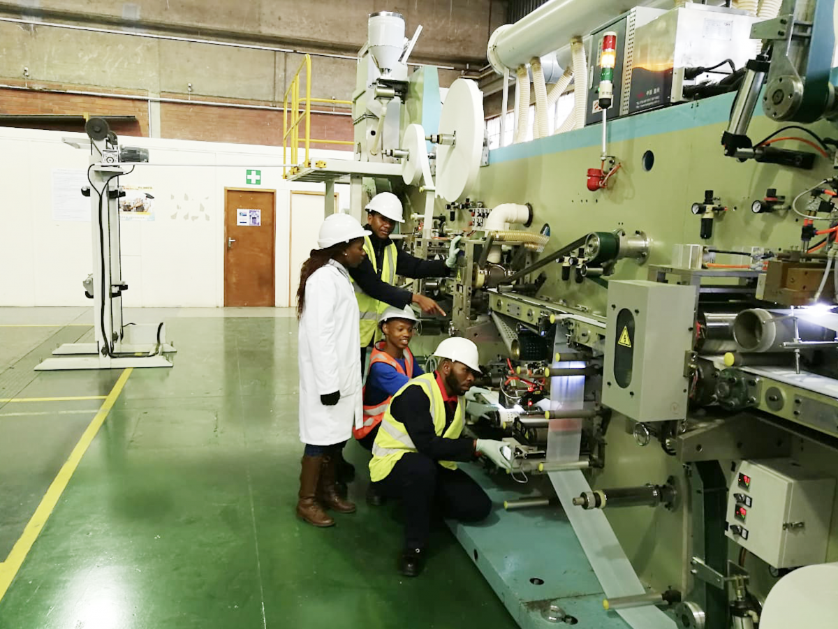 Technicians working on the machine that produces sanitary towels at Coastal College Skills Training Centre.