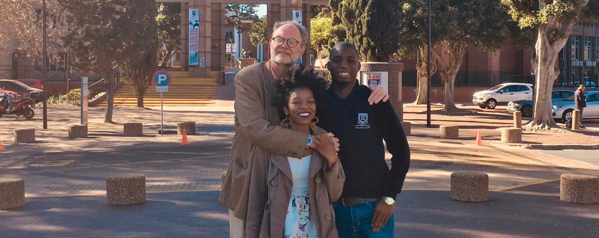 Theo Krynauw with two Sparklekids Tinashe Nyamurowa and Bonke Xakata who are studying at university.