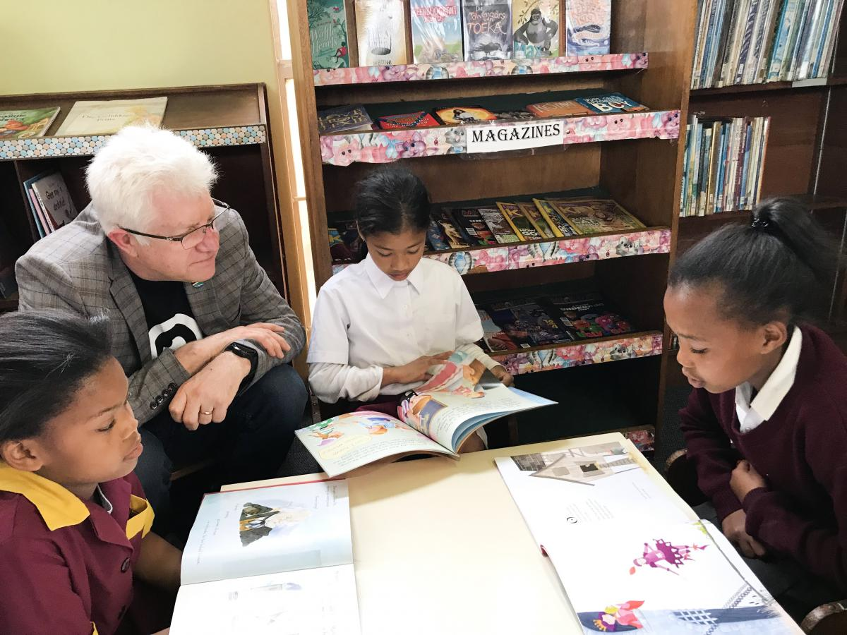 Children from Hanover Park read to Western Cape Premier Alan Winde at a ceremony where books were donated.