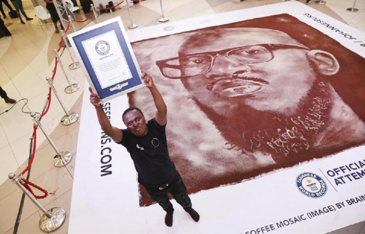 Artist Percy Maimela holds his certificate from Guinness World Records after creating a mosaic out of ground coffee beans of artist Black Coffee
