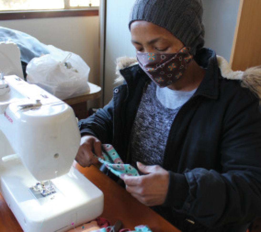 A public-private maskmaking initiative is giving community seamstresses a small income while also providing masks for disadvantaged people.