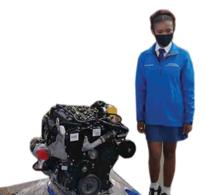 Otto Du Plessis High School pupil Agnes Farret next to an engine donated by Ford to her school.