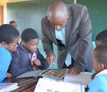 Mathematics teacher Lungisa Khanyile shows his learners how to use an iPad.