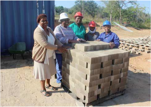 Members of the Tfutfukani Brick making cooperative stand proudly next to the material they produce. The business is doing well and has potential to grow. (Photo: Mduduzi Tshabangu)