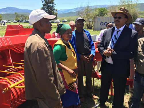 MEC Mlibo Qoboshiyane with beneficiaries of the drought relief programme standing in front of the equipment donated by the Department of Rural Development and Agrarian Reform.